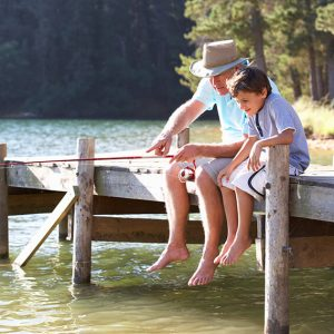 Grandparent fishing with grandchild