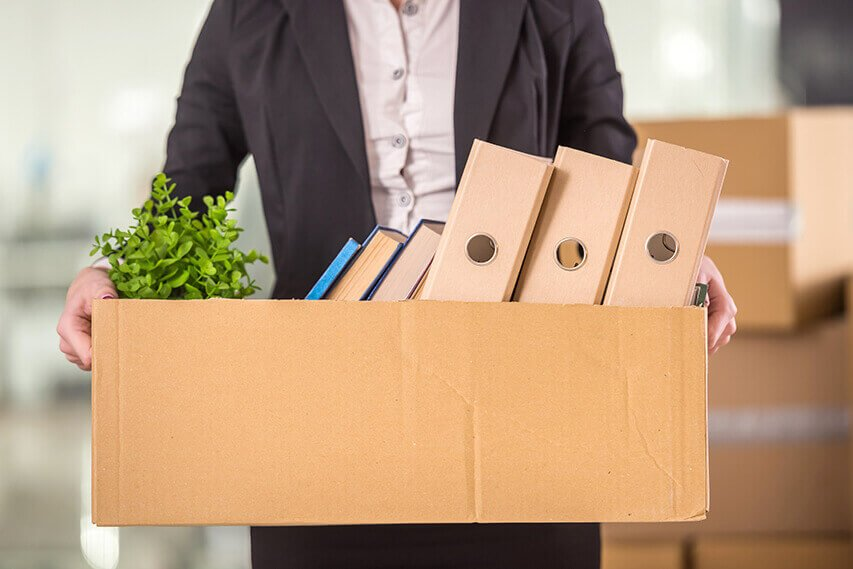 Retiree forced to give up work early, holding a box a box of belongings.