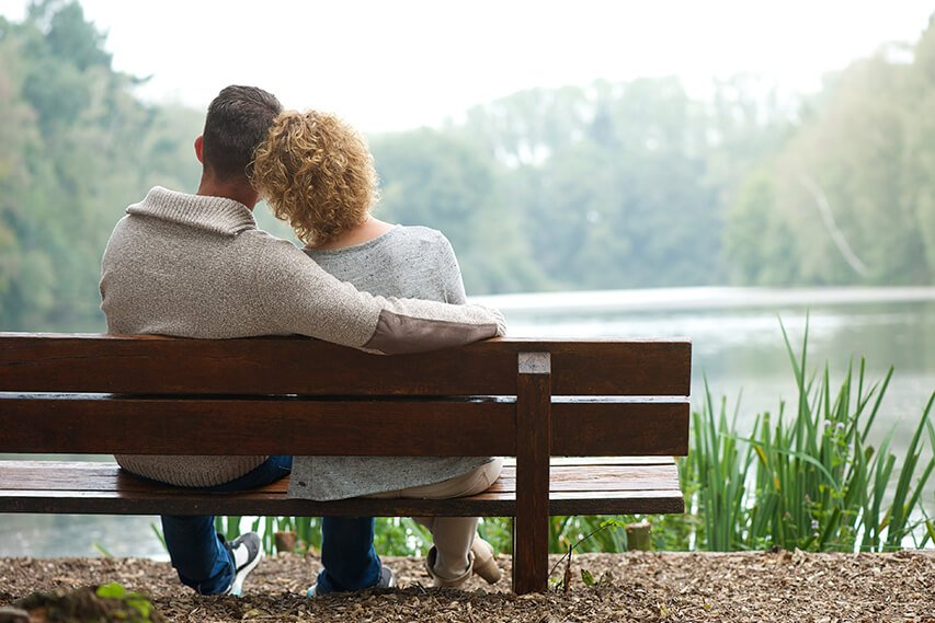 Couple enjoying a comfortable retirement, pictured sitting by a lake.