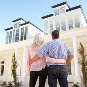 Retired homeowners standing outside their property considering their property wealth