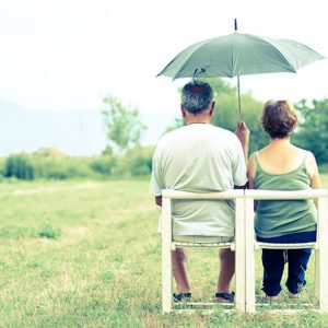 Retirees sitting under an umbrella