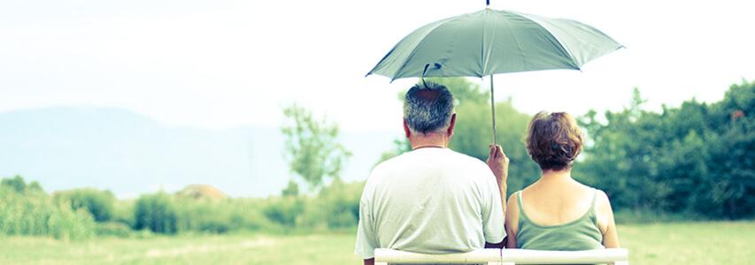 Retirees sitting under an umbrella