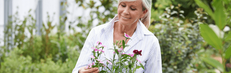 mature woman choosing plants from garden centre